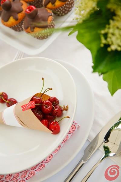 I piatti bianchi con i muffin e le ciliegie
