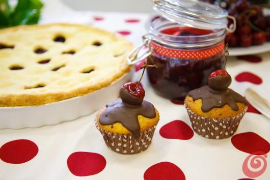 I muffin con le ciliegie sulla tovaglia bianca a grossi pois rossi.