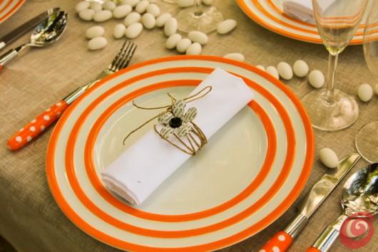 Un fiore di carta stampata sui piatti bianchi bordati di arancio: il matrimonio in arancio
