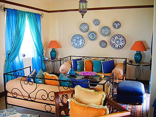 Un salotto addobbato con dei tipici souvenir: i piatti, i cuscini e i tessuti. La soluzione d'arredo non decade nel banale, ma mantiene una nota di ricercatezza e originalità.