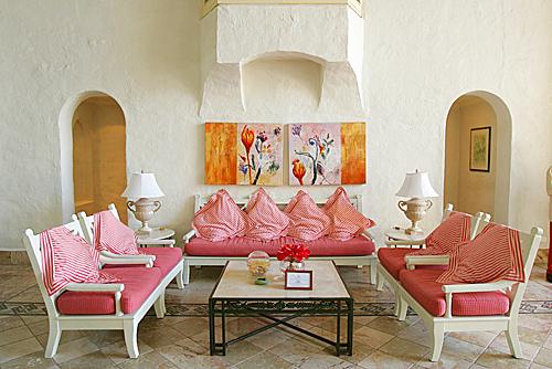 Un salotto dalle pareti fresche e candide, ravvivato dai cuscini e dalle stoffe vivaci