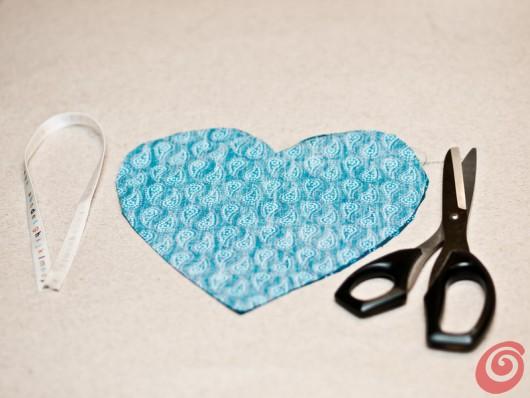 Il tessuto a forma di cuore per cucire un portaspilli o un profumatore.