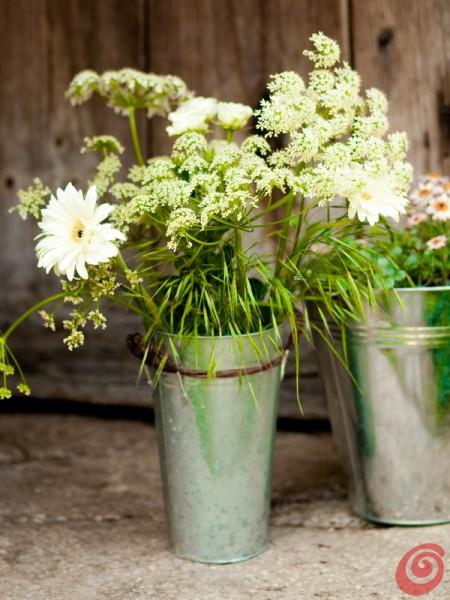 La decorazione floreale con il vaso zincato, i fiori coltivati e i fiori di campo