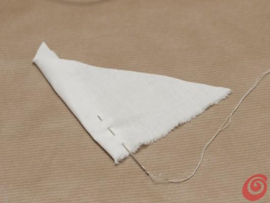 Un pezzo di tela bianca farà da vela alla barchetta per la decorazione della tavola apparecchiata in stile marinaro.