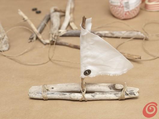 Infiliamo la vela sull'albero della nostra barchetta per la decorazione fai da te per la tavola apparecchiata in stile marinaro.