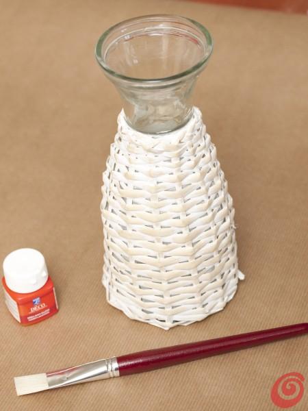Una bottiglia rivestita di vimini farà da faro per la nostra decorazione fai da te per la tavola apparecchiata alla marinara.