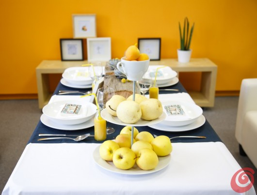 La tavola apparecchiata in blu e in giallo è perfettamente intonata alla parete color arancio.