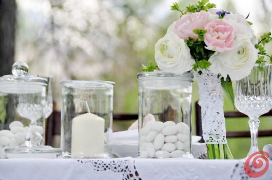 I confetti bianchi e la candela nei vasi di vetro, i colori pastello del bouquet, la tovaglia bianca in pizzo - la tavola apparecchiata per il matrimonio bianco