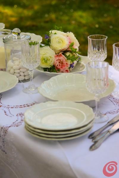 I piatti bianchi, i bicchieri in cristallo e le posate sulla tovaglia bianca in pizzo per la tavola apparecchiata per un matrimonio un po' vintage