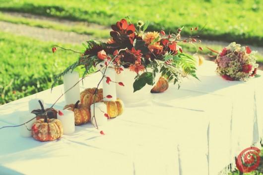 Idee per la decorazione autunnale fai da te: fiori, zucche e candele sulla tovaglia bianca