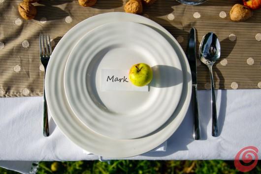 La tavola apparecchiata autunnale: mele e frutta secca come decorazione