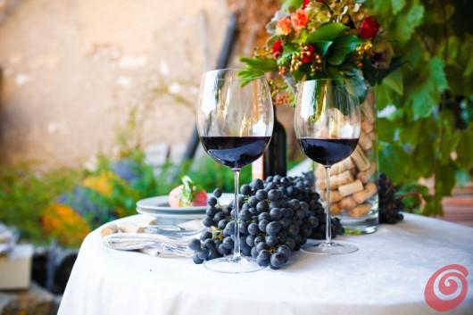 decorare la tavola autunnale con calle porpora, bouqut autunnale, vino terrano e prosciutto