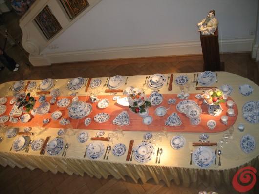 la tavola apparecchiata con un servizio di Meissen con il classico motivo di cipolle fiorite, completo di statuine decorative e complementi, la foto è stata ripresa nel museo della manifattura di Meissen presso Dresda, Germania